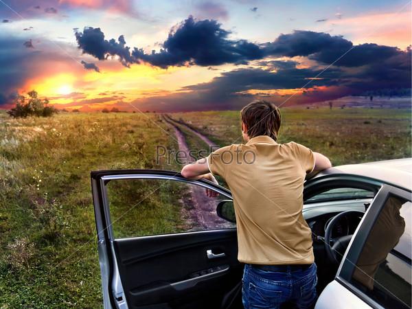 Парень стоит возле автомобиля и смотрит на закат