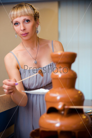 Красивая молодая женщина ест шоколадное фондю