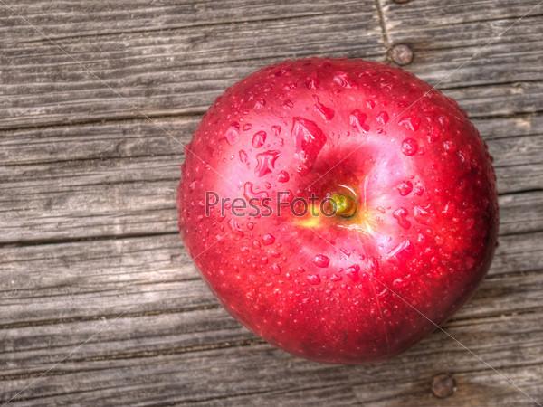 Яблоко с каплями воды на столе