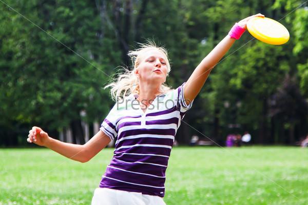 Молодая и красивая женщина играет во фрисби в парке