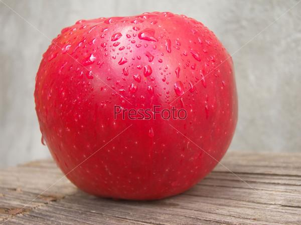Красное яблоко с каплями воды