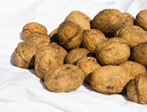 Грецкие орехи на белой ткани