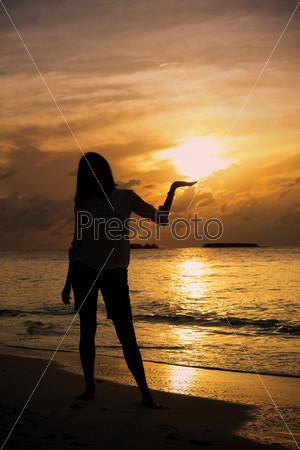 Силуэт девушки на закате возле побережья Индийского океана
