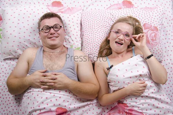Парень и девушка в очках лежат в постели и улыбаются