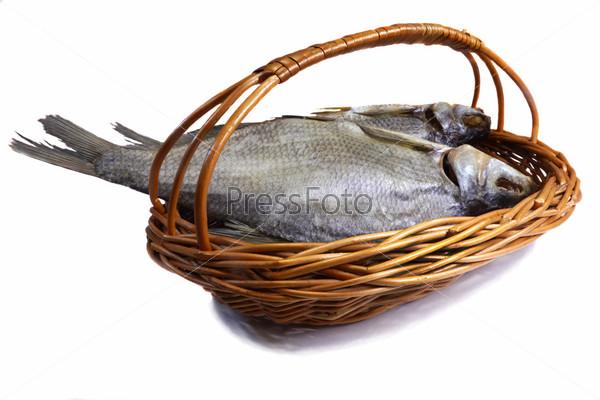 Солено-сушеная речная рыба в корзине на белом фоне