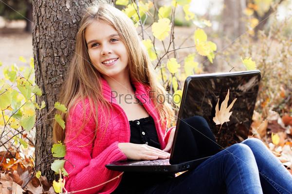 Красивая девочка в осеннем парке с ноутбуком