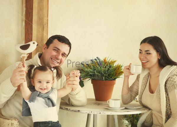 Фотография на тему Счастливая семья с годовалой дочерью пьет кофе