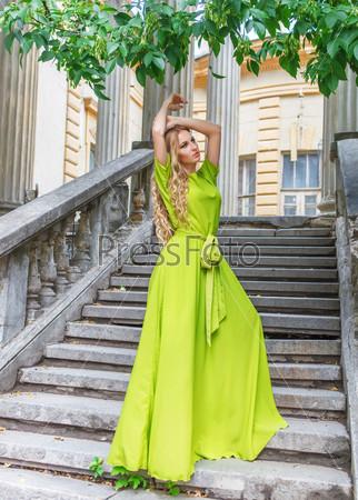 Красивая женщина в длинном зеленом платье на открытом воздухе