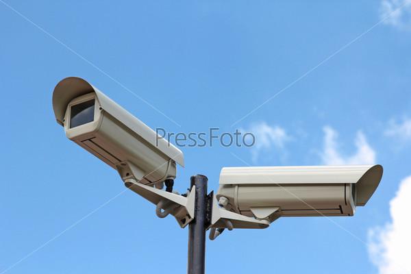 Две камеры безопасности на фоне голубого неба