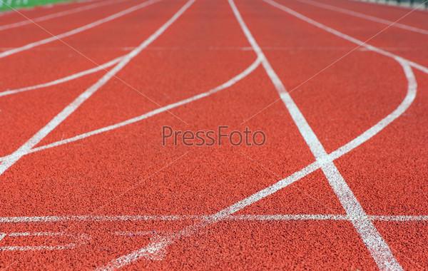 Красная беговая дорожка на стадионе с белыми линиями
