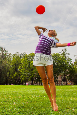 Фотография на тему Молодая и красивая женщина играет в волейбол