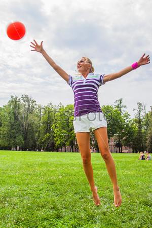 Молодая и красивая женщина играет в волейбол