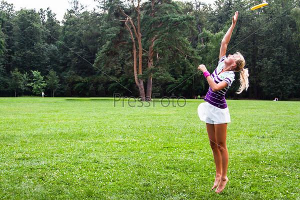 Молодая и красивая женщина играет с фрисби в парке