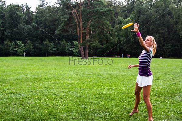 Фотография на тему Молодая и красивая женщина играет с фрисби в парке