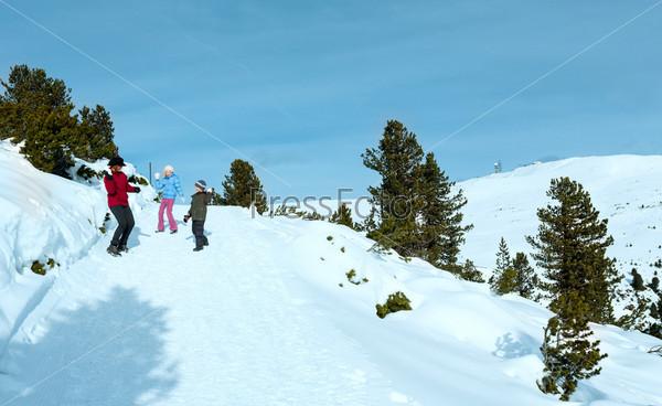 Фотография на тему Семья играет в снежки на склоне горы зимой