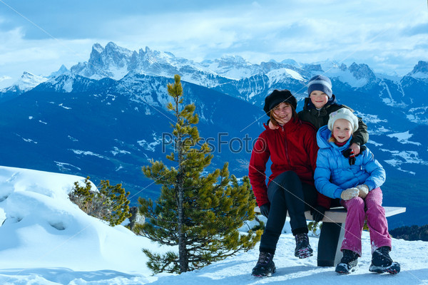 Фотография на тему Семью гуляет на склоне горы зимой