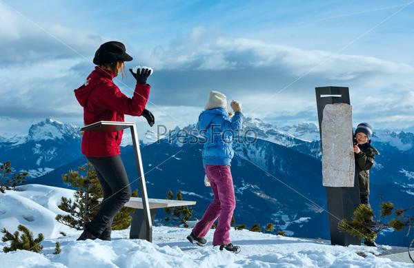 Семья играет в снежки на склоне горы зимой