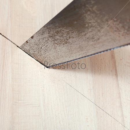Фотография на тему Деревянную доску режут ножовкой
