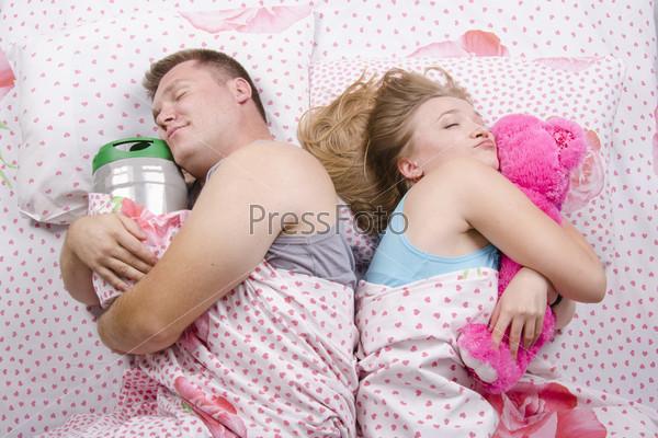 Спящая пара в постели: она обнимает мягкую игрушку, он бочонок пива