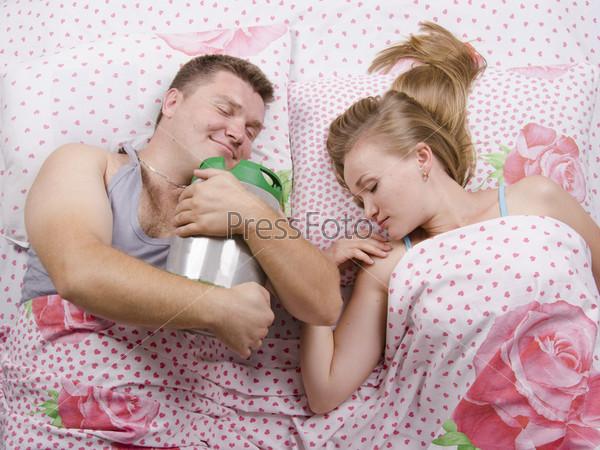 Жена и довольный муж с бочонком пива спят в постели