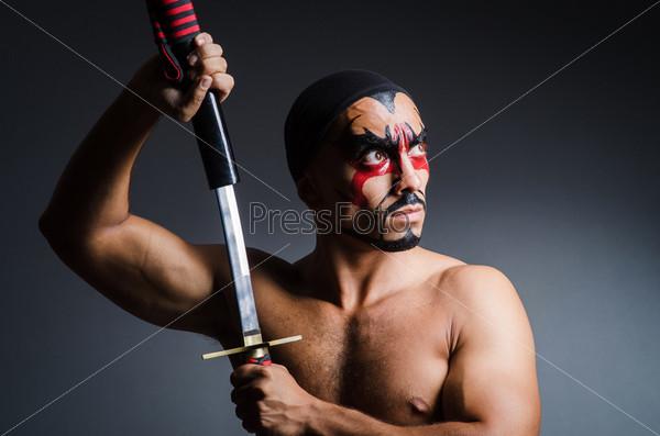 Фотография на тему Человек с мечом и раскрашенным лицом