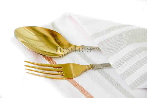 Ложка и вилка на льняной салфетке