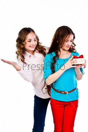 Красивая девочка дарит другой девочке подарок