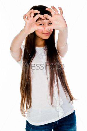 Маленькая и красивая девочка показывает пальцами сердце