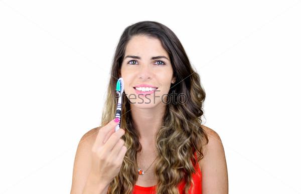 Красивая молодая женщина показывает зубную щетку и улыбается
