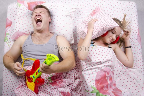 Фотография на тему Пара в постели. Жена спит накрывшись подушкой, муж играет на гитаре