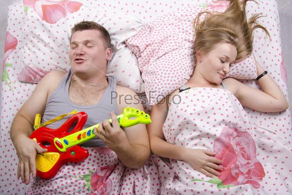 Пара в постели. Жена спит, муж играет на гитаре