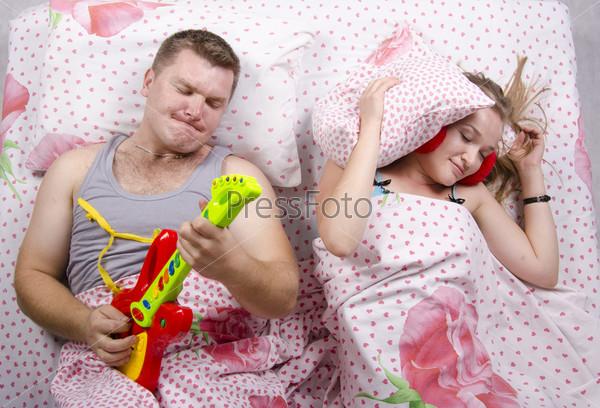 Пара в постели. Жена спит накрывшись подушкой, муж играет на гитаре