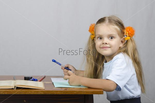 Фотография на тему Маленькая девочка сидит за столом и пишет в тетради