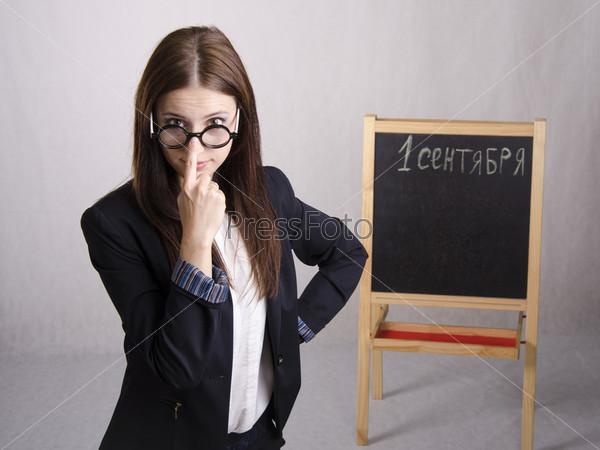 Школьный учитель поправляет очки на носу