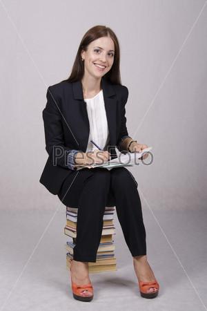 Фотография на тему Школьный учитель сидит на учебниках и проверяет тетради учеников
