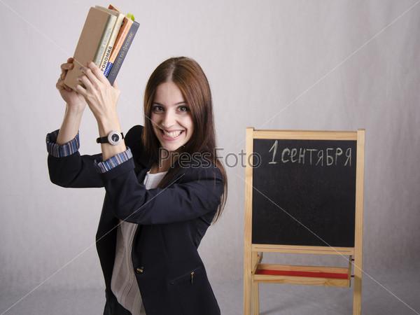 Школьный учитель весело подняла стопку учебников
