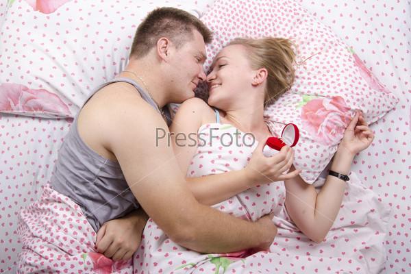 Парень дарит девушке кольцо, лежа в постели