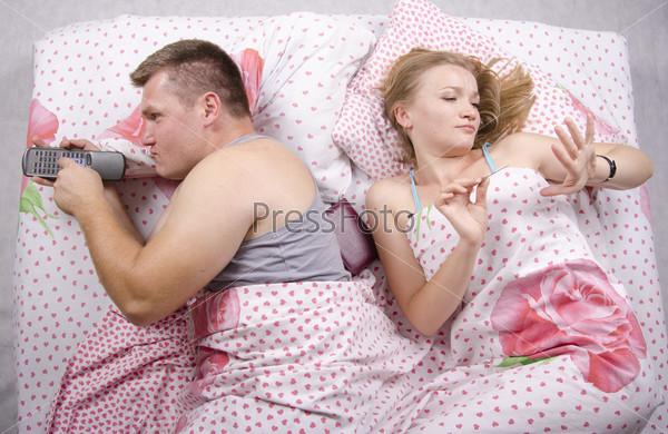 Пара в постели. Он с пультом лежит на боку, она обрабатывает ногти