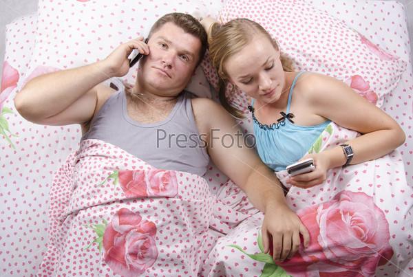 Пара лежит в постели. Она пишет смс, он разговаривает по телефону