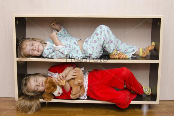 Двое детей лежат на полках тумбочки