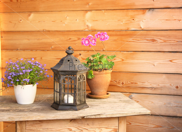 Фотография на тему Цветы и старый фонарь на деревянном столе