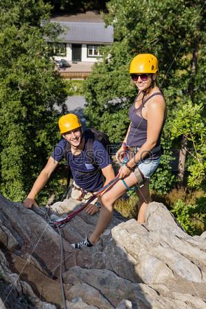 Альпинисты со страховочным оборудованием отдыхают на скале
