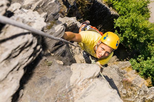 Молодой человек поднимается на скалу