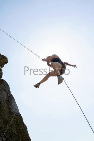 Женщина поднимается на скалу
