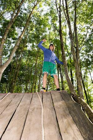 Человек празднует успех после восхождения по деревянной горке