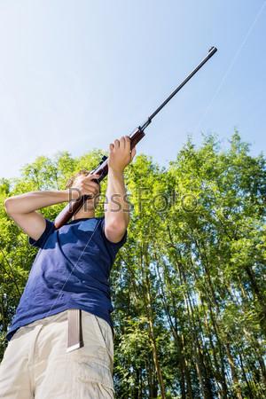 Человек с винтовкой охотится в лесу