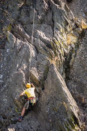 Фотография на тему Молодой человек поднимается на скалу
