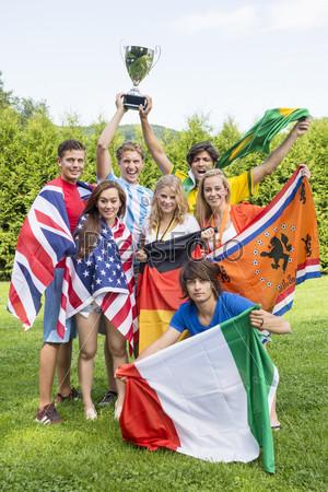 Спортсмены с различными национальными флагами, празднующие в парке