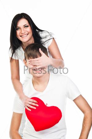 Молодая и красивая женщина дарит мужчине плюшевое сердце
