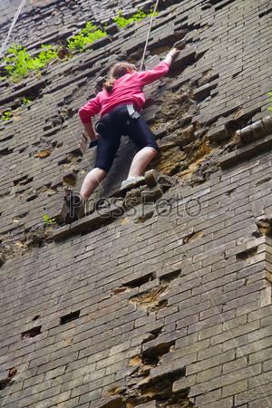 Молодая женщина поднимается по кирпичной стене